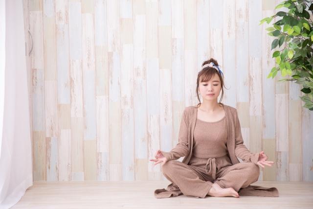 瞑想のヨガのポーズをとり、気持ちをリフレッシュ、リラックスさせている落ち着いた時間を過ごす女性のイメージ画像。