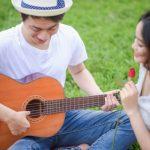 ピクニックでギターを弾いて歌を歌って楽しんでいる男女のイメージ。