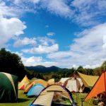 天気に恵まれた日に屋外でのキャンプイベントに大勢の方が参加されていることがイメージできるテントがたくさん張られた広大で緑豊かな草原の広場の様子
