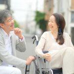 車椅子の女性の話をしっかり聞いて何を求められているかを笑顔で理解しようと思ったいる男性のイメージ