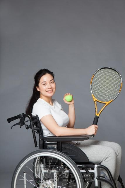 車いすテニスにチャレンジしようとしている笑顔の女性の明るくてさわやかで活動的な画像。情報にもバリアフリーを。障がい者とその関係者のコミュニティ、情報サイト。ナレバリ