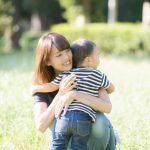 2歳の子供と公園で遊んでいる中で愛情をもって優しく抱きかかえるお母さんのイメージ。情報にもバリアフリーを。障がい者とその関係者のコミュニティ、情報サイト。ナレバリ