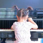 慣れない手つきながらピアノを一生懸命に練習している小さな女の子のイメージ画像。情報にもバリアフリーを。障がい者とその関係者のコミュニティ、情報サイト。ナレバリ