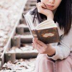 秋の枯れ葉が落ちる公園で読書を楽しむ女性のイメージ画像。情報にもバリアフリーを。障がい者とその関係者のコミュニティ、情報サイト。ナレバリ