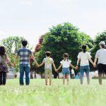 三世代家族が仲良く原っぱで手をつなぐ写真。情報にもバリアフリーを。障がい者とその関係者のコミュニティ、情報サイト。ナレバリ