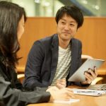 会社のミーティングで笑顔で議論する男女のイメージ画像。情報にもバリアフリーを。障がい者とその関係者のコミュニティ、情報サイト。ナレバリ