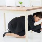 地震が起こり机の下に避難する女性。情報にもバリアフリーを。障がい者とその関係者のコミュニティ、情報サイト。ナレバリ