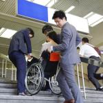 バリアフリー対策をしていない階段や段差のあるところで車椅子を補助している人たちの様子