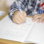 子供が鉛筆で学習ノートに文字を書く練習をしている、書き取りの練習をしているイメージ画像。