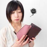 財布の中身を見て、見辛く困っているような表情の女性の画像。情報にもバリアフリーを。障がい者とその関係者のコミュニティ、情報サイト。ナレバリ