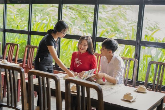 広々とした空間があり車椅子でも楽しめそうなベトナム料理店で民族衣装アオザイを着て楽しそうにメニューの内容を店員に聞いている交際中と思しき男女のイメージ画像。