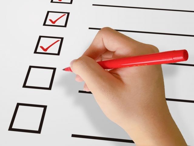 ホワイトボードを使って自分の予定を一つ一つ確認し終わったものに対してチェックマークを入れている時間管理をしている人の様子。情報にもバリアフリーを。障がい者とその関係者のコミュニティ、情報サイト。ナレバリ