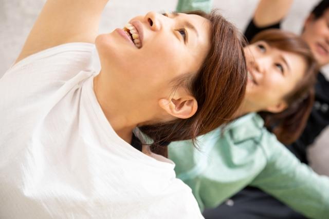 お友達同士で体を動かす体操を晴れやかな笑顔で楽しんでいる女性たちのさわやかなイメージ画像。