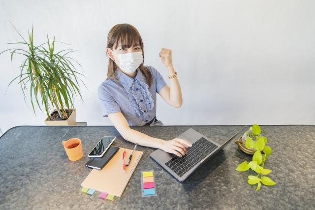 仕事場においても新型コロナウィルス対策のためマスクをしながらも新しいことにもチャレンジする気持ちで仕事を頑張ろうと前向きになっている女の子のイメージ。