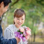 恋愛関係にある男性から花束を受け取りプロポーズをされて喜んでいる女性のイメージ。