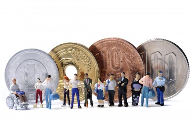 コインの前で様々な人のミニチュアが並んで列をなしているお金にまつわるイメージ画像。情報にもバリアフリーを。障がい者とその関係者のコミュニティ、情報サイト。ナレバリ
