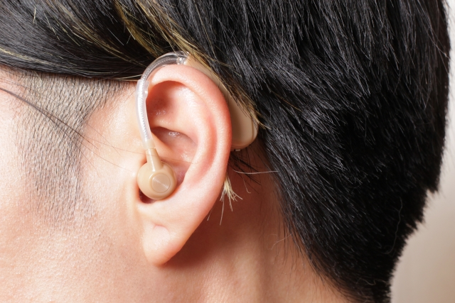 コンパクトな補聴器を耳につけている男性のイメージ写真。情報にもバリアフリーを。障がい者とその関係者のコミュニティ、情報サイト。ナレバリ
