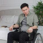 何かに怒りを感じイライラした表情を見せる車いすの男性。情報にもバリアフリーを。障がい者とその関係者のコミュニティ、情報サイト。ナレバリ
