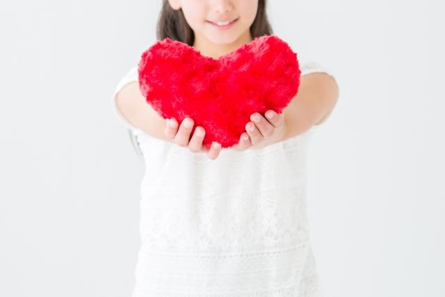 赤いハートを持ち愛の告白を明るい表情でしている女性のイメージ画像。情報にもバリアフリーを。障がい者とその関係者のコミュニティ、情報サイト。ナレバリ
