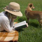 原っぱでリラックスしながら愛犬と読書を楽しみ女性の画像。情報にもバリアフリーを。障がい者とその関係者のコミュニティ、情報サイト。ナレバリ