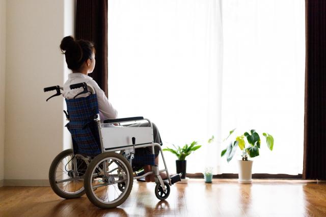 車いすに乗り自宅の窓辺で外の景色を見ている女性の画像。情報にもバリアフリーを。障がい者とその関係者のコミュニティ、情報サイト。ナレバリ