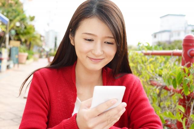 スマートフォンでSNSを利用して微笑む女性のイメージ画像。情報にもバリアフリーを。障がい者とその関係者のコミュニティ、情報サイト。ナレバリ