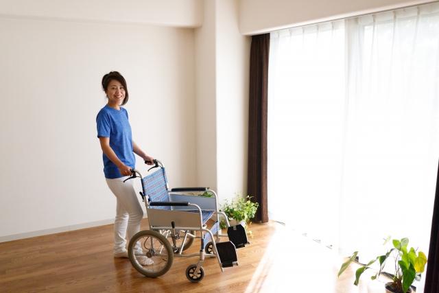 車いすを手に部屋でたたずむ女性。情報にもバリアフリーを。障がい者とその関係者のコミュニティ、情報サイト。ナレバリ